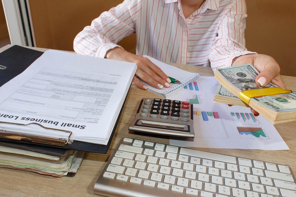Frau mit Geldbündel in der Hand an Schreibtisch mit Unterlagen, Tastatur und Taschenrechner